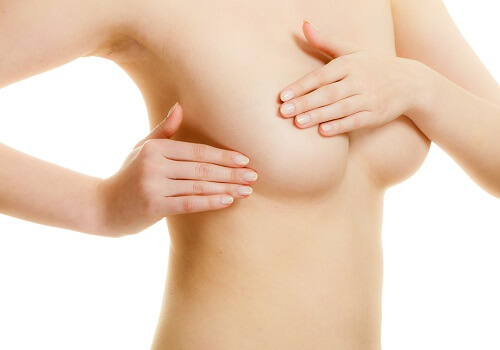 Health care medical concept. Young woman examining her breasts for lumps or signs of breast cancer isolated on white